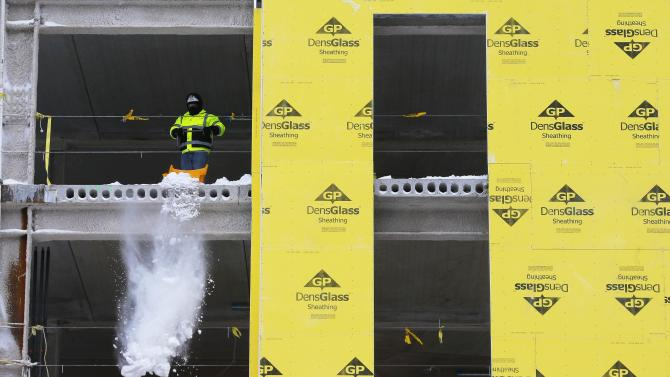 A worker clears snow out of a building under construction in Cambridge
