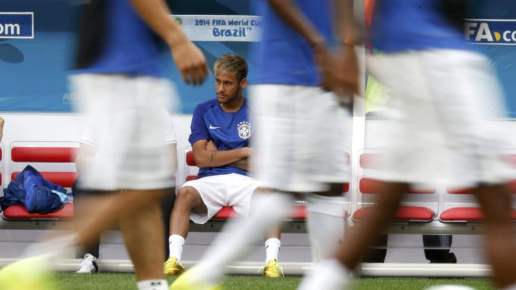 Brazil's Neymar watches his teammates warm up hefore the 2014 World Cup third-place playoff between Brazil and the Netherlands at the Brasilia national stadium