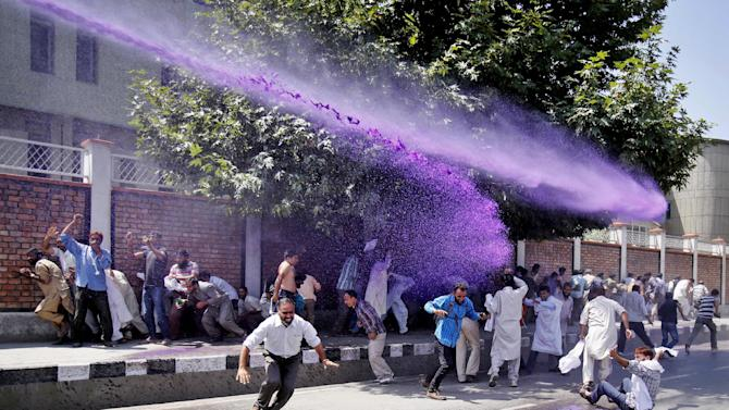 Colored water from a police water cannon hits Kashmiri government employees as they shout slogans during a protest in Srinagar, India, Thursday, Aug 21, 2014. Police used force to disperse Kashmiri government employees during the protest demanding regularization of contractual jobs and a hike in salary. (AP Photo/Mukhtar Khan)
