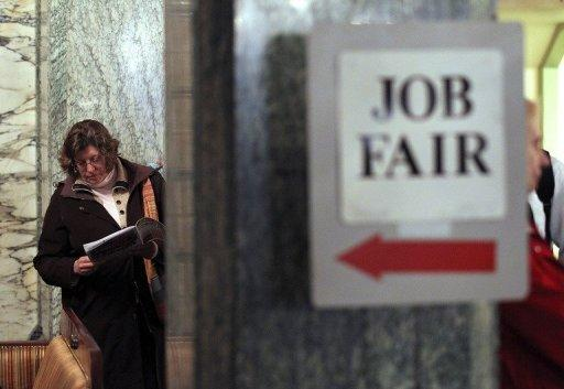 A job seeker looks over event materials as she waits to enter a San Francisco job fair