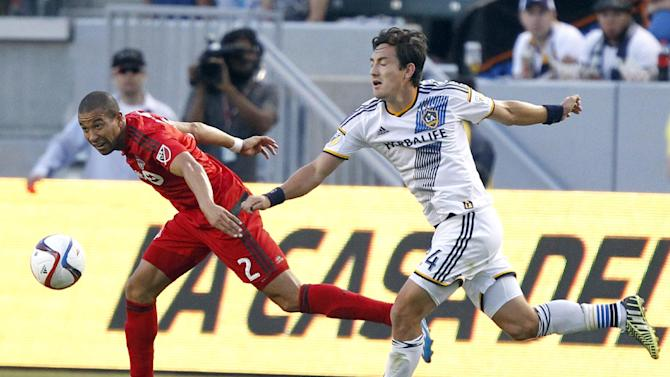 Toronto FC defender Justin Morrow, left, and Los Angeles Galaxy midfielder Stefan Ishizaki race for the ball during the first half of an MLS soccer game in Carson, Calif., Saturday, July 4, 2015. The Galaxy won 4-0. (AP Photo/Alex Gallardo)