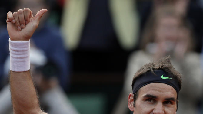 Switzerland's Roger Federer thumbs up after defeating France's Gille Simon in their fourth round match of the French Open tennis tournament at the Roland Garros stadium Sunday, June 2, 2013 in Paris. (AP Photo/Petr David Josek)