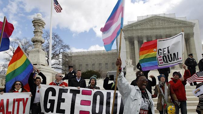 FILE - In this March 27, 2013 file photo, demonstrators hold flags and chant in front of the Supreme Court in Washington on the second day of gay marriage cases before the court. The Supreme Court's landmark ruling on same-sex marriage has private employers around the country scrambling to make sure their employee benefit plans comply with the law. The impact of the decision is somewhat clear in the 13 states and the District of Columbia where gay marriage is currently legal - same-sex married couples must be treated the same as other spouses under federal laws governing tax, health care, pensions and other federal benefits. (AP Photo/Jose Luis Magana, File)