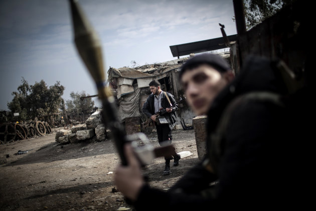 Free Syrian Army fighters hold their weapons during heavy clashes with government forces in Aleppo, Syria, Sunday, Jan. 20, 2013. The revolt against President Bashar Assad began in March 2011with peac