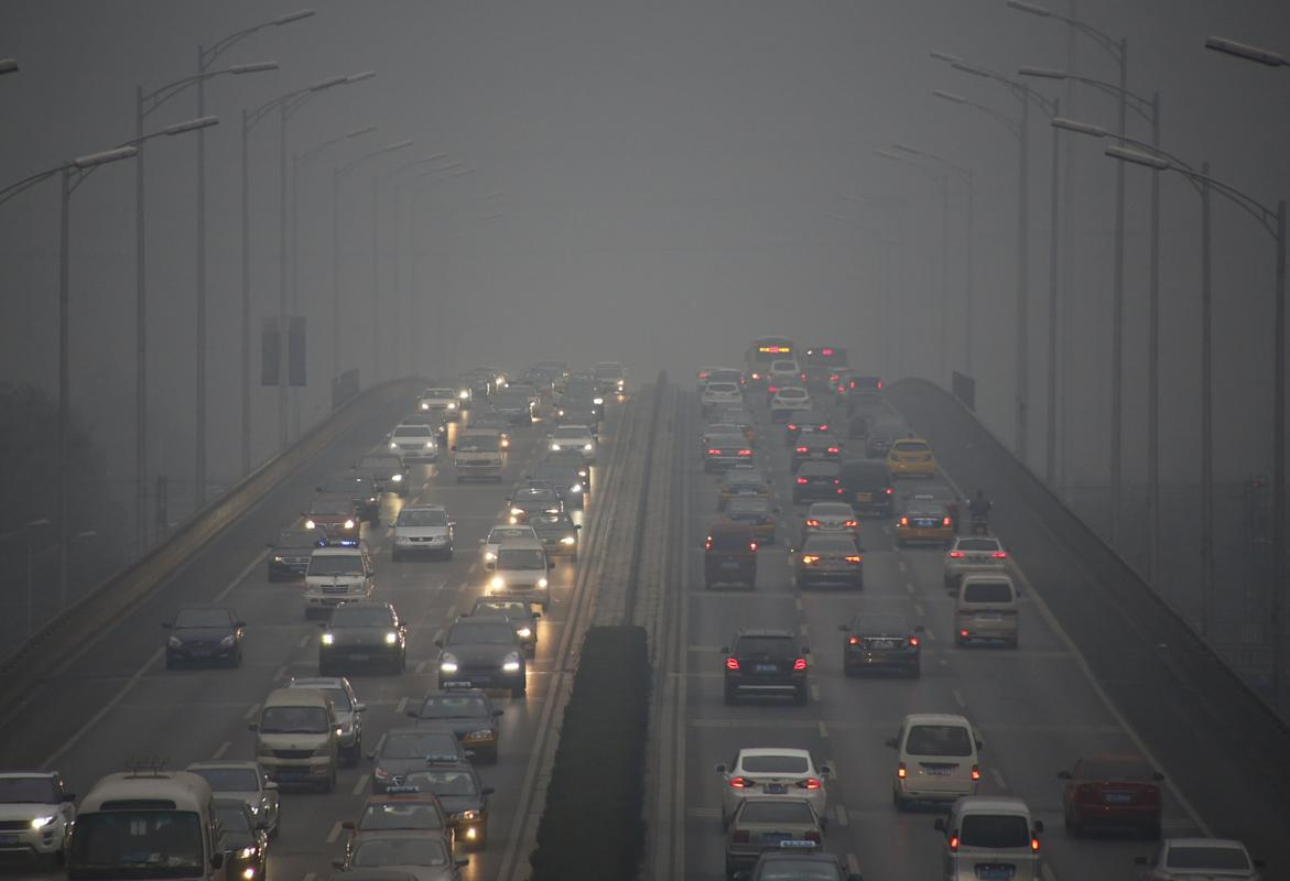 "Vehicles using lights travel on a bridge amid heavy smog after the city issued its first ever ""red alert"" for air pollution, in Beijing"