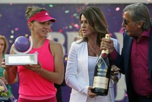 Romanian former gymnast Comaneci and former tennis player Nastase offer a champagne bottle to compatriot Halep as she holds the trophy of the BRD Bucharest Open international tennis tournament in Bucharest