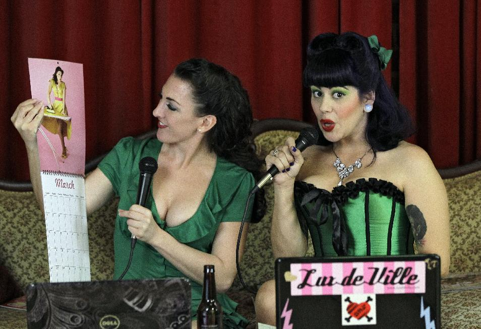 "In this March 5, 2012, photo, Nicole Nadreau, left, who goes by the stage name of  ""Contessa"" and Christina Farsciello, who goes by ""Judy Pop"", look at a pinup calendar during their Internet show in an Ybor City studio in Tampa, Fla. (AP Photo/Chris O'Meara)"