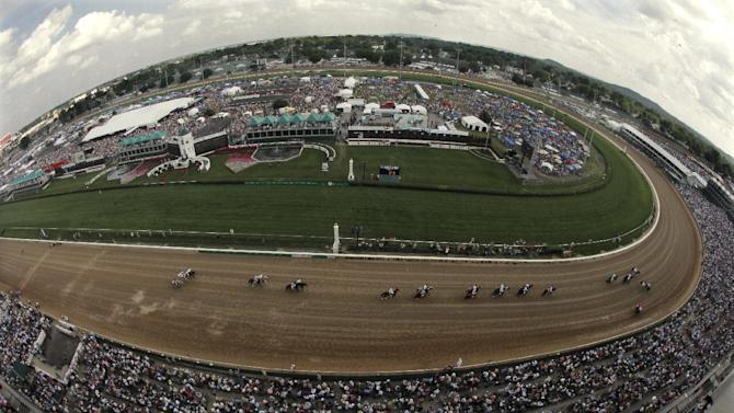 In a photo taken with a fisheye lens, jockeys and their horses make their way past the grand stand at the Churchill Downs before the 10th race at 138th Kentucky Derby horse race Saturday, May 5, 2012, in Louisville, Ky. (AP Photo/Charlie Riedel)