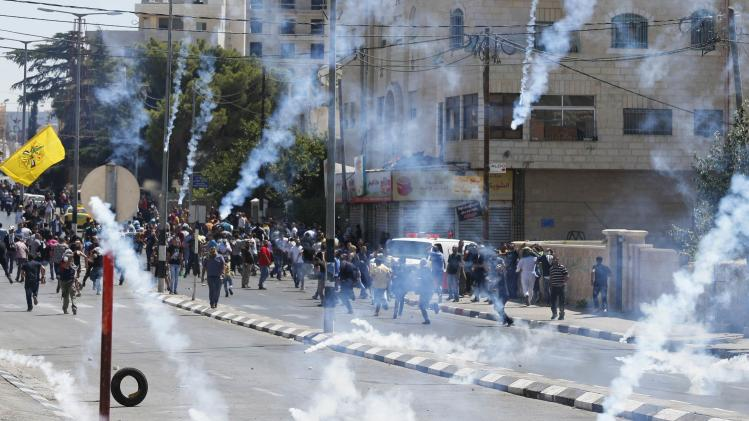 Palestinian protesters run after Israeli troops fired tear gas during clashes at a protest against the Israeli offensive in Gaza, in the West Bank town of Bethlehem