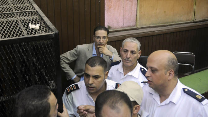"""Islam Afifi, the chief editor of  el-Dustour newspaper, center, attends a court hearing in Cairo, Egypt, Thursday, Aug. 23, 2012. A Cairo court on Thursday ordered the chief editor of an Egyptian newspaper detained pending trial on charges of insulting the country's president and """"spreading lies."""" The case against Afifi of the privately-owned el-Dustour daily is one of several lawsuits brought mainly by Egypt's Islamists against journalists, accusing them of inflammatory coverage and inciting the public against the Muslim Brotherhood, the country's largest political group. (AP Photo/Mohammed Asad)"""