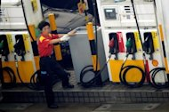 A petrol station worker motions toward an incoming car in Hong Kong in 2009. China, the world&#39;s second-biggest oil consumer, said it would cut fuel prices by more than three percent, following a retreat in global crude costs and amid concerns over inflation