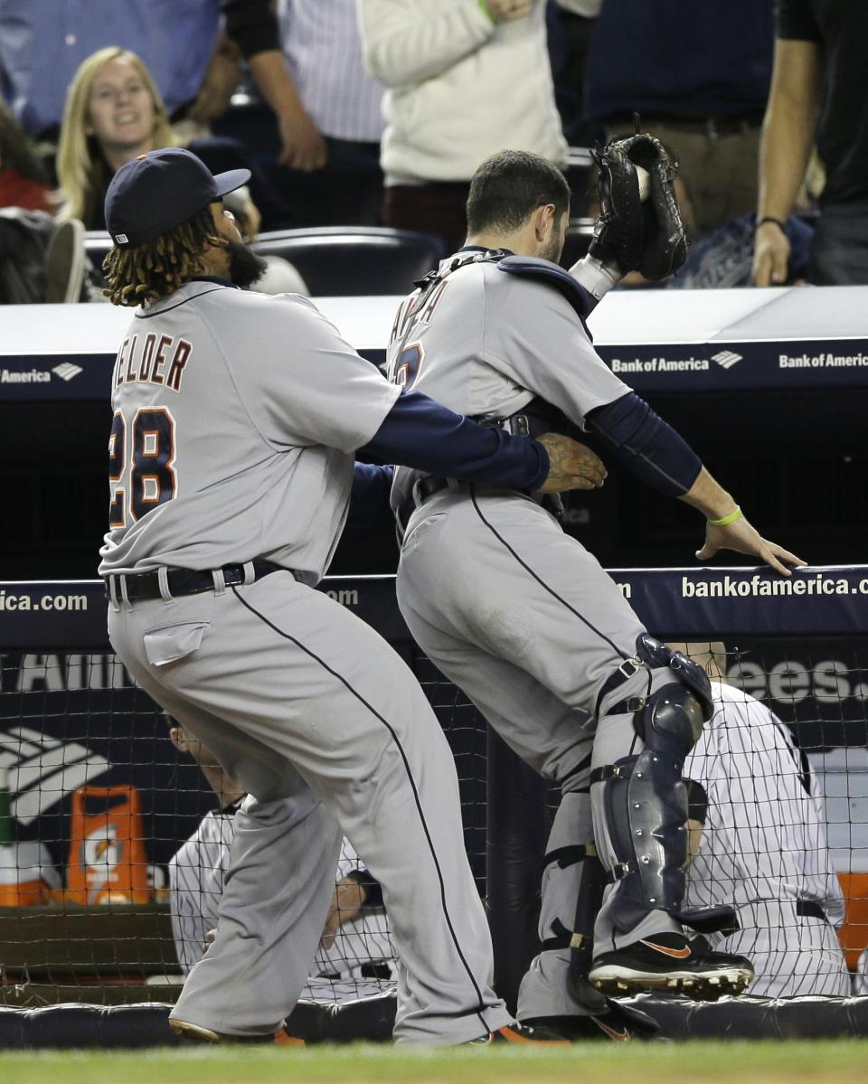 Detroit Tigers' Prince Fielder holds catcher Alex Avila after Avila caught a foul ball by New York Yankees' Mark Teixeira for the final out in the eighth inning of Game 2 of the American League championship series Sunday, Oct. 14, 2012, in New York. (AP Photo/Matt Slocum)