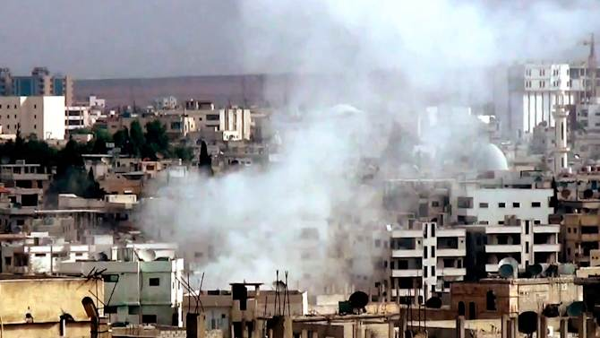 This image taken from video obtained from the Shaam News Network, which has been authenticated based on its contents and other AP reporting, purports to show smoke rising from buildings due to government forces shelling in Daraa, Syria, on Tuesday, Oct. 2, 2012. (AP Photo/Shaam News Network via AP video)