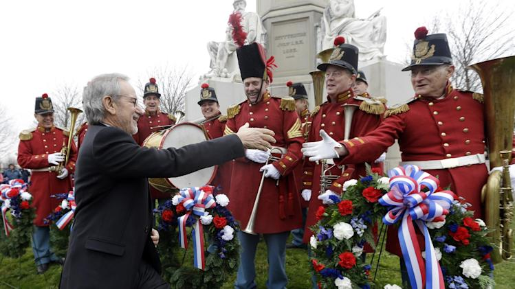 "Director Steven Spielberg, left, greets members of ""The President's Own Band,"" a musical group of Civil War re-enactors, during a ceremony to mark the 149th anniversary of President Abraham Lincoln's delivery of the Gettysburg Address at Soldier's National Cemetery in Gettysburg, Pa., Monday, Nov. 19, 2012. Spielberg and historian Doris Kearns Goodwin were also on hand to deliver remarks and participate in a wreath-laying ceremony. (AP Photo/Patrick Semansky)"
