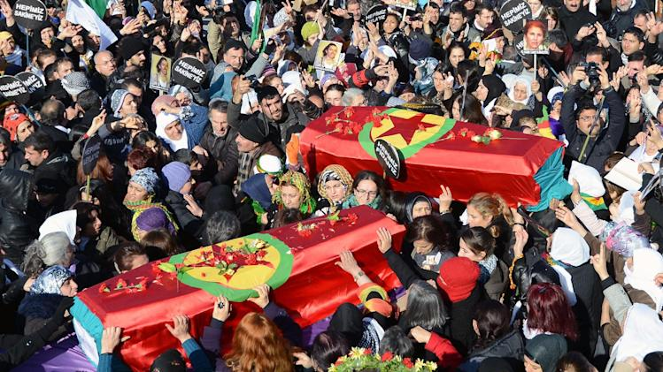 People carry the coffins of three Kurdish activists as tens of thousands of people gather for their funeral in Diyarbakir, sourtheastern Turkey, Thursday, Jan. 17, 2013. The three women activists, including a founding member of the outlawed Kurdistan Workers' Party, or PKK, were found shot dead in Paris last week at a time when Turkey is holding peace talks with the rebels' jailed leader. Many believe the killings may be an effort to derail the talks. (AP Photo)