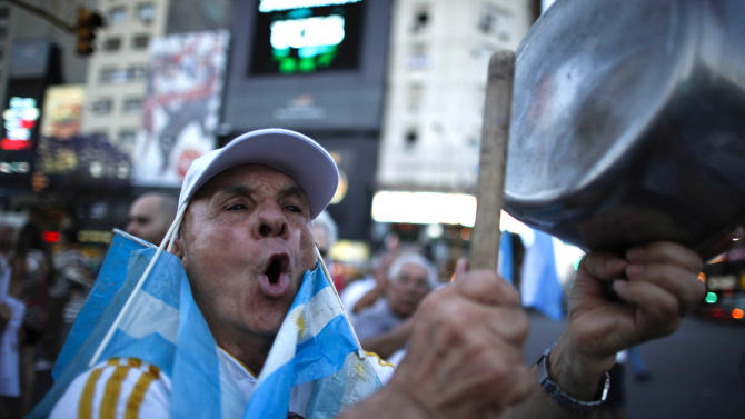A protester bangs a pot during a march against Argentina's President Cristina Fernandez in Buenos Aires, Argentina, Thursday, Nov. 8, 2012. Angered by rising inflation, violent crime and high-profile corruption, and afraid Fernandez will try to hold onto power indefinitely by ending constitutional term limits, the protesters banged pots and marched on the iconic obelisk in Argentina's capital. Protests also were held in plazas nationwide and outside Argentine embassies and consulates around the world. (AP Photo/Natacha Pisarenko)