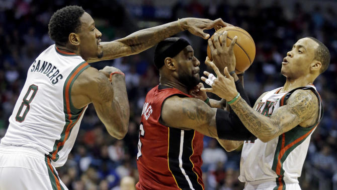 Milwaukee Bucks' Larry Sanders (8) and Monta Ellis, right, try to steal the ball from Miami Heat's LeBron James during the first half of Game 3 in their first-round NBA basketball playoff series on Thursday, April 25, 2013, in Milwaukee. (AP Photo/Morry Gash)