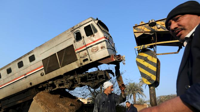 Egyptian workers remove the wreckage of a train crash in Beni Suef