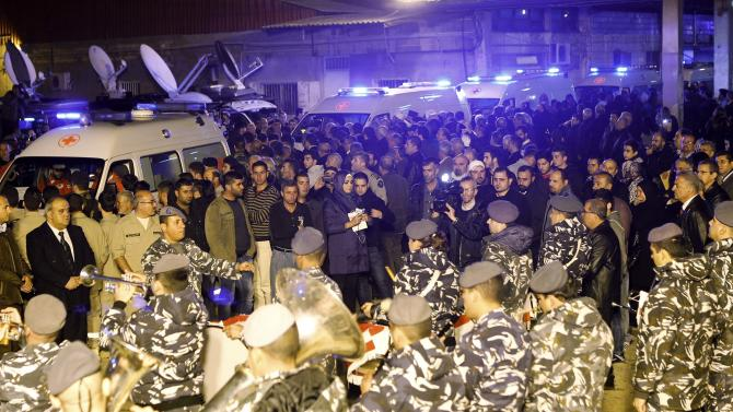 Lebanese Internal Security Forces play instruments as ambulances drive by carrying the bodies of Lebanese victims of the Air Algerie flight AH5017 crash, at the Beirut international airport