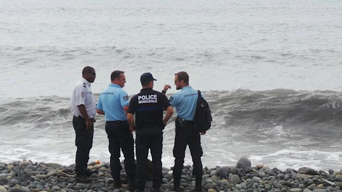 French gendarmes and police stand on the beach where a large piece of plane debris was found in Saint-Andre, on the French Indian Ocean island of La Reunion