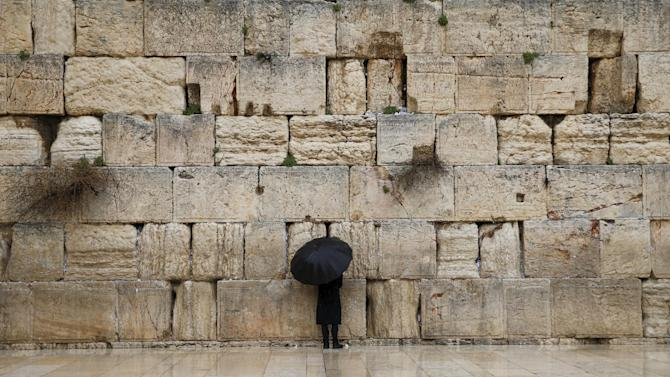 An Orthodox Jewish man holds an umbrella as he stands next to the Western Wall, Judaism's holiest prayer site, on a rainy day in Jerusalem's Old City