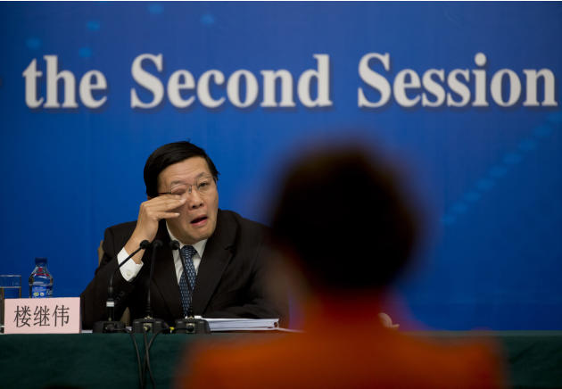 China's Finance Minister Lou Jiwei, rubs his eye as he listens to a question from a reporter at a news conference during the annual meeting of China's legislature in Beijing, China Thursday, March 6,