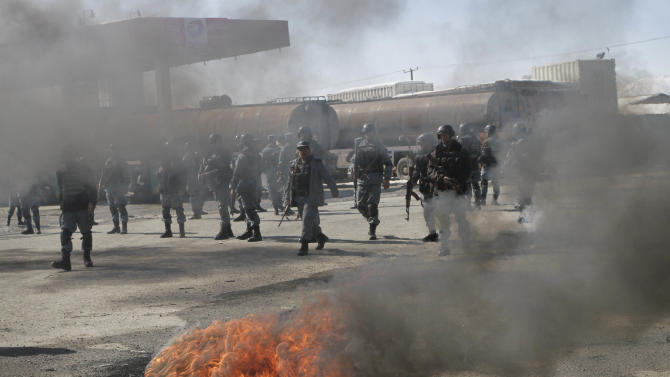 Black smoke rises from tyres which were burnt by protesters as Afghan policemen march during an anti-US demonstration in Kabul, Afghanistan, Wednesday, Feb. 22, 2012. Police say anti-American demonstrations are under way on the outskirts of the Afghan capital and in another city over an incident that the U.S. says was inadvertent burning of Muslim holy books at a military base. (AP Photo/Musadeq Sadeq)