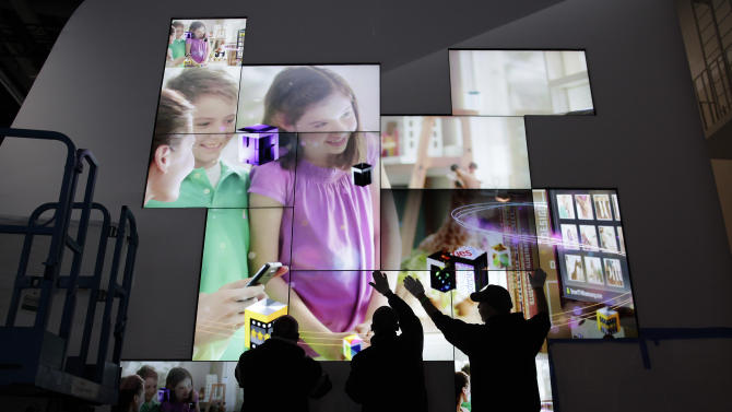 Workers set up a flat screen display at the Samsung exhibit for the Consumer Electronics Show, Monday, Jan. 9, 2012, in Las Vegas.  The 2012 International CES trade show, the world's largest consumer electronics exhibition starts Tuesday. (AP Photo/Julie Jacobson)