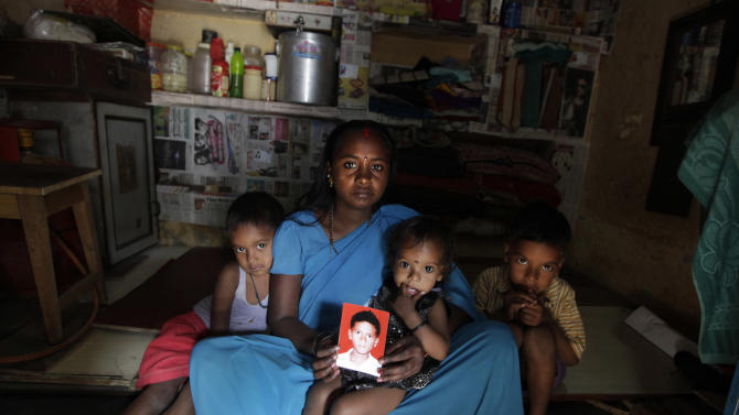 In this Monday, March 25, 2013 photo, Pinky Devi shows the picture of her son Ravi Shankar, who disappeared three years ago, while sitting with her sons, Rahul, 7, right, Ramesh, 5, left, and a daughter Sandhya, 18 months, in her lap, in their one room tenement, in New Delhi, India. Ravi is among the more than 90,000 children who go missing in India each year. More than 34,000 of them are never found, the government said last year. (AP Photo/ Manish Swarup)