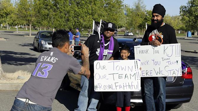 Sacramento Kings fan Tony Duong, far left, takes a picture of his son Ethan, 9, center, with fellow fans Peter Masih, left, and Bik Dusangh before an NBA basketball game against the Los Angeles Clippers in Sacramento, Calif., Wednesday, April 17, 2013. NBA Commissioner David Stern said Wednesday that a decision on the future home of the Kings franchise is still at least two weeks away. (AP Photo/Rich Pedroncelli)