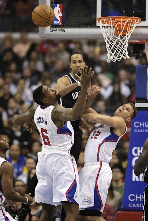 Brooklyn Nets' Shaun Livingston, top, passes the ball as he is defended by Los Angeles Clippers' DeAndre Jordan, left, and Blake Griffin during the first half of an NBA basketball game on Saturday, No