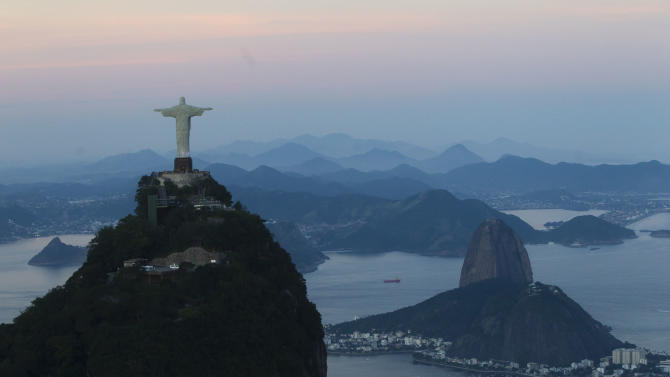 FILE - In this May 10, 2012 file photo, the Christ the Redeemer statue stands back dropped by Sugar Loaf mountain, right, as the sun sets in Rio de Janeiro, Brazil. The Olympic flame goes out in London on Sunday, Aug. 12, 2012, and all eyes turn to Rio, which in 2016 will become the first South American city to host the Games.  (AP Photo/Felipe Dana, File)