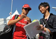 Ferrari driver Fernando Alonso of Spain (L) signs his autograph for a fan at the paddock during the Formula One Japanese Grand Prix at the Suzuka circuit, on October 7. Alonso later spun out of the race, at the first corner