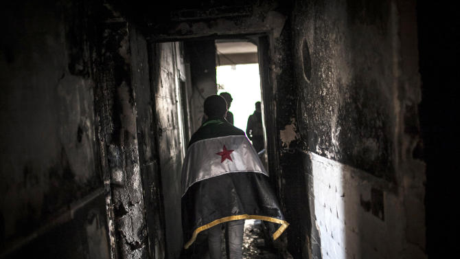 Syrian civilians, one draped in the revolutionary flag, walk through the ruins of a destroyed home in Aleppo, Syria, Thursday, Jan. 3, 2013. The area is immersed in a Syrian civil war that the United Nations estimates has killed more than 60,000 people since the revolt against President Bashar Assad began in March 2011. (AP Photo/Andoni Lubaki)