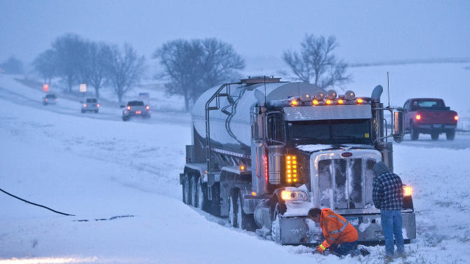 A towing crew from Moody's of Rochester, Minn. hooks up a tanker trailer truck that lost control and landed in the median of U.S. 52 North near Oronocco, Minn. Thursday, Dec. 20, 2012.  The first major snowstorm of the season began its slow eastward march across the Midwest early Thursday, creating treacherous driving conditions and threatening to disrupt some of the nation's busiest airports ahead of the holiday weekend.(AP Photo/ Rochester Post-Bulletin, Jerry Olson)