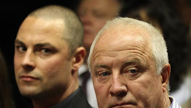 Olympic athlete Oscar Pistorius' father Henke Pistorius, right, with his son Carl watch as Oscar Pistorius walks in during his bail hearing at the magistrate court in Pretoria, South Africa, Friday, Feb. 22, 2013. (AP Photo/Themba Hadebe)