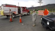 <p>               FILE - In this Friday, June 15,2012 file photo Army National Guardsmen Spc. Rachel Cornett, right, and Sgt. Timothy Apodaca let a fire truck pass their road block leading to the Poudre Canyon on  the High Park wildfire west of Fort Collins, Colo. Colorado has some of the tightest restrictions on news media coverage of wildfires, keeping reporters miles away from burn areas and erecting barriers to access to officials in the know and as well as victims. (AP Photo/Ed Andrieski,File)