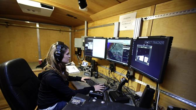 This photo taken March 26, 2013, shows Insitu unmanned aircraft system flight test operator Hannah Rasmussen monitoring controls in a ground control station in Arlington, Ore.  It's a good bet that in the not-so-distant future aerial drones will be part of Americans' everyday lives, performing countless useful functions. A far cry from the killing machines whose missiles incinerate terrorists, these generally small unmanned aircraft will help farmers more precisely apply water and pesticides to crops, saving money and reducing environmental impacts. They'll help police departments to find missing people, reconstruct traffic accidents and act as lookouts for SWAT teams. They'll alert authorities to people stranded on rooftops by hurricanes, and monitor evacuation flows.  (AP Photo/Don Ryan)