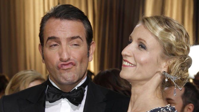 Actor Jean Dujardin, left, and Alexandra Lamy arrive before the 84th Academy Awards on Sunday, Feb. 26, 2012, in the Hollywood section of Los Angeles. (AP Photo/Amy Sancetta)