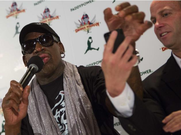 Former NBA basketball player Rodman reaches for a mobile phone during a news conference in New York