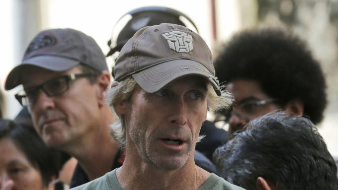 """American film director Michael Bay speaks with his film crew during the filming of a scene for their latest movie """"Transformers 4: Age of Extinction"""" in Hong Kong Friday, Oct. 18, 2013. Bay was attacked on Thursday and slightly injured on the set of the fourth installment of the """"Transformers"""" movie series filming in Hong Kong, police said. The spokeswoman said Bay suffered a minor injury to his face but declined medical treatment. (AP Photo/Kin Cheung)"""
