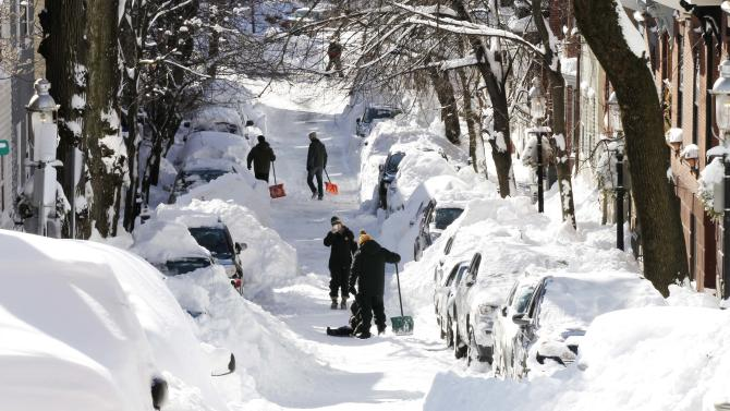 People pause for a picture while digging out their cars in Boston, Sunday, Feb. 10, 2013. A howling storm across the Northeast left the New York-to-Boston corridor shrouded in 1 to 3 feet of snow Saturday, stranding motorists on highways overnight and piling up drifts so high that some homeowners couldn't get their doors open. More than 650,000 homes and businesses were left without electricity.(AP Photo/Winslow Townson)