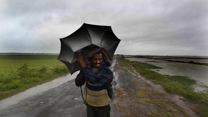 An Indian villager braving strong winds and rain walk to a safer place, in village Podampeta, in Ganjam district about 200 kilometers (125 miles) from the eastern Indian city Bhubaneswar, India, Saturday, Oct. 12, 2013. Strong winds and heavy rains pounded India's eastern coastline Saturday, as hundreds of thousands of people took shelter from a massive, powerful Cyclone Phailin expected to reach land in a few hours. (AP Photo/Biswaranjan Rout)