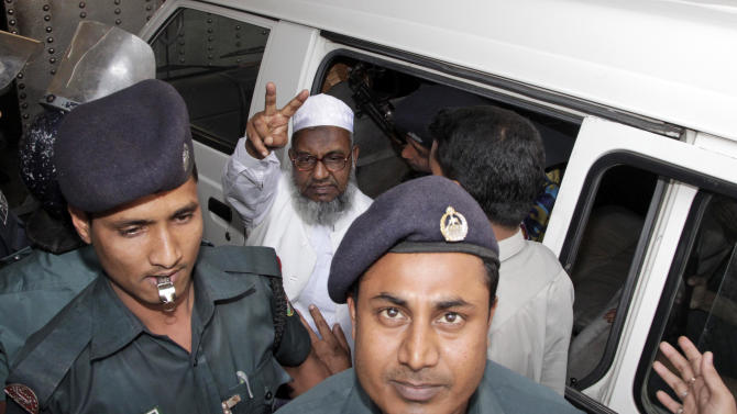 In this Feb. 5, 2013 photo, Jamaat-e-Islami leader Abdul Quader Mollah displays the victory sign, escorted by policemen, after he was sentenced to life in prison for killings and other crimes during the nation's independence war, in Dhaka, Bangladesh. Mollah, an assistant secretary of Jamaat, was found guilty of killing a student and a family of 11 and of aiding Pakistani troops in killing 369 others. Members of his party took to the streets in anger at his conviction, exploding homemade bombs and clashing with police. But they were soon overshadowed by thousands of protesters who flooded a major intersection in the capital, Dhaka, upset at what they said was a lenient verdict and inflamed by the image of Mollah smiling at journalists and holding up two fingers in a ''V'' sign as he left the court.  (AP Photo/Zia Islam)