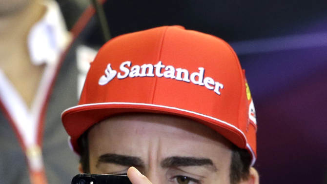 Ferrari driver Fernando Alonso, of Spain, takes a picture during a news conference at the Circuit of the Americas race track Thursday, Nov. 15, 2012, in Austin, Texas. Formula One's U.S. Grand Prix auto race is scheduled for Sunday at the track. (AP Photo/David J. Phillip)