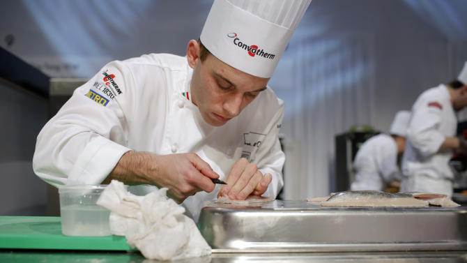 """Gabor Molnar, of Hungary, prepares food during the """"Bocuse d'Or"""" (Golden Bocuse) trophy, at the 15th World Cuisine contest, in Lyon, central France, Wednesday, Jan. 28, 2015. The contest, a sort of world cup of the cuisine, was started in 1987 by Lyon chef Paul Bocuse to reward young international culinary talents. (AP Photo/Laurent Cipriani)"""
