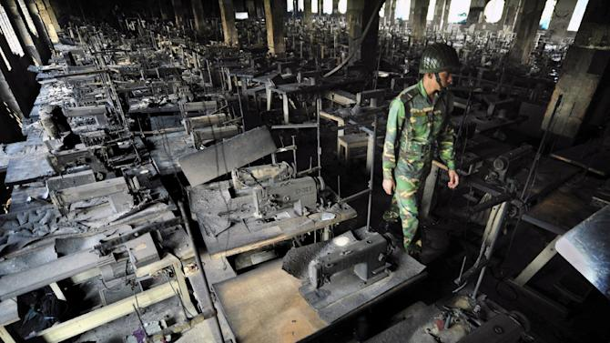 "FILE - In this Nov. 25, 2012 file photo, a Bangladeshi police officer walks between rows of burnt sewing machines in a garment factory outside Dhaka, Bangladesh. About a year before the fire at the factory killed 112 people, executives from Wal-Mart, Gap and other big clothing companies met nearby in the country's capital to discuss a legally binding contract that would govern safety inspections. But after a spokeswoman for Wal-Mart, the world's largest retailer, got up and said the proposal wasn't ""financially feasible,"" the effort quickly lost momentum. AP Photo/Khurshed Rinku, File)"