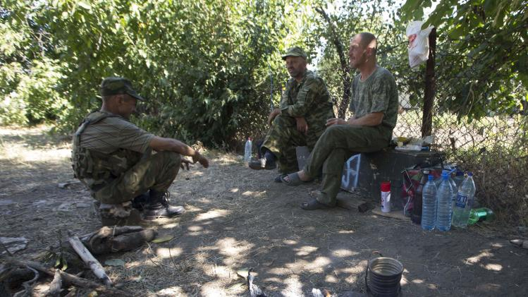 Armed pro-Russian separatists rest in the southern coastal town of Novoazovsk