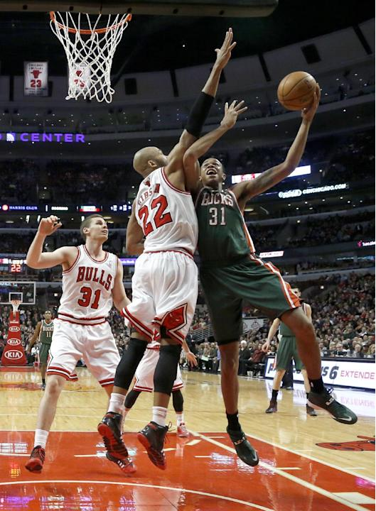 Milwaukee Bucks forward John Henson (31) shoots over Chicago Bulls forward Taj Gibson (22) as Erik Murphy (31) watches during the second half of an NBA basketball game Tuesday, Dec. 10, 2013, in Chica