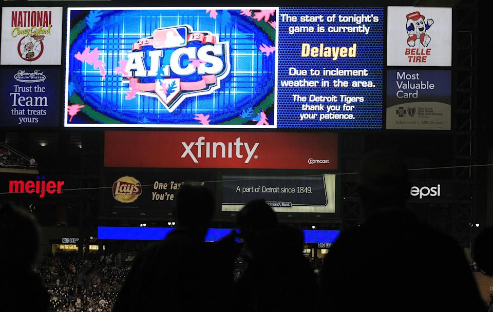 Fans wait as Game 4 of the American League championship series between the Detroit Tigers and New York Yankees is delayed due to weather Wednesday, Oct. 17, 2012, in Detroit. (AP Photo/Carlos Osorio)
